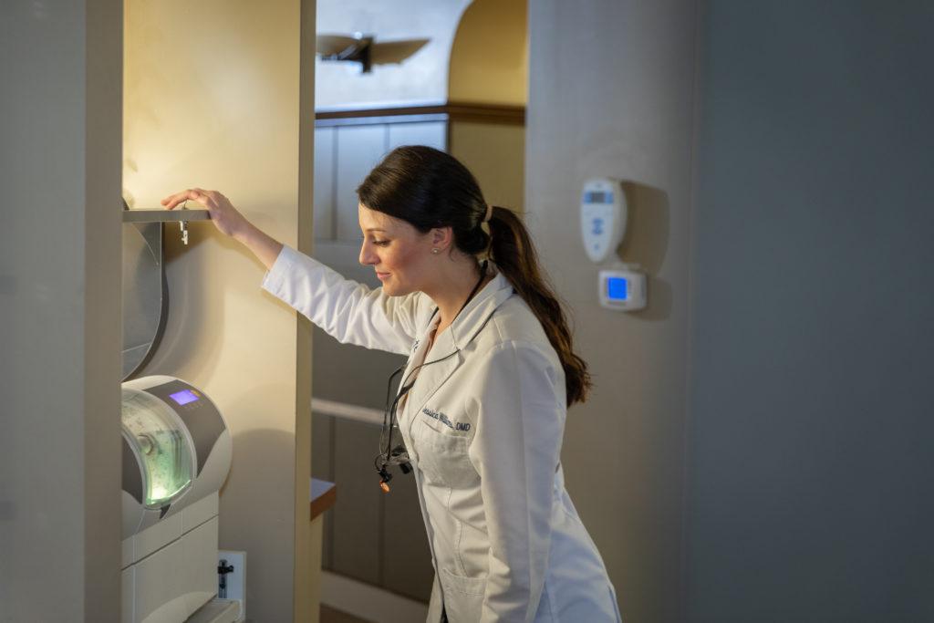 Woman dentist using dental equipment